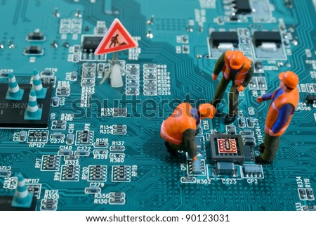 Miniature engineers fixing error on chip of motherboard. Computer repair concept. Close-up view. - stock photo