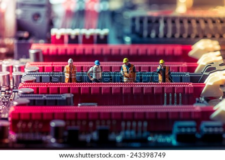 Miniature engineers repairing circuit board. Technology concept - stock photo