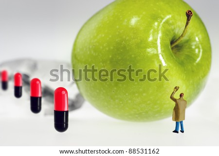 miniature figure in front of a big green apple and four capsules - stock photo