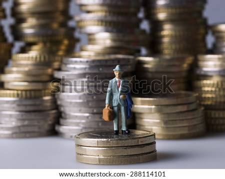 Miniature figure standing on a pile of coins. - stock photo