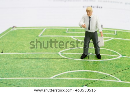 miniature figurine of a football coach teaching a green football field