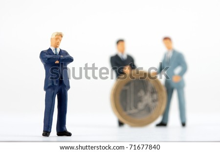 Miniature figurine of successful businessman with team on background - stock photo