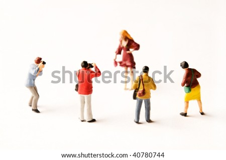 miniature figurines of photographers with a  model on white background - stock photo