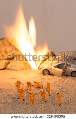 Miniature firemen at a car accident scene in flames - stock photo