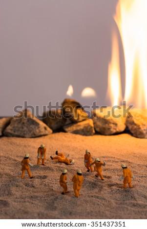 Miniature firemen at work near a real fire - stock photo