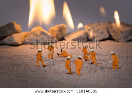 Miniature firemen at work near a real fire close up - stock photo