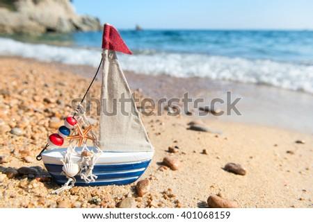 Miniature fishing boat at beach - stock photo