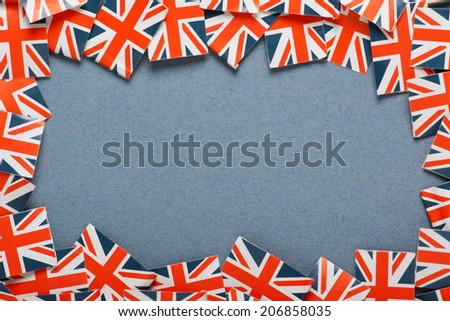 Miniature flags of the United Kingdom arranged to form a border on a blue paper background with copy space - stock photo