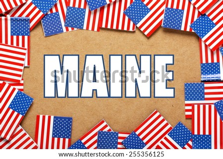 Miniature flags of the United States of America form a border on brown card around the name of the state of Maine - stock photo