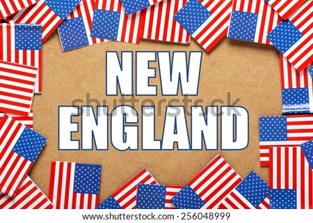 Miniature flags of the United States of America form a border on brown card around the name of the region of New England - stock photo