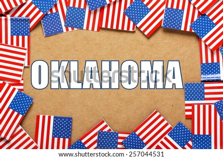 Miniature flags of the United States of America form a border on brown card around the name of the state of Oklahoma - stock photo