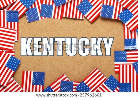 Miniature flags of the United States of America form a border on brown card around the name of the state of Kentucky - stock photo