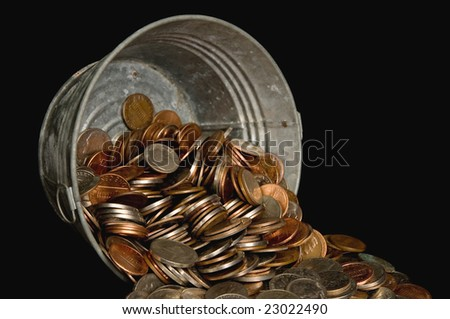 Miniature galvanized wash tub with American coins spilling out, black iso. - stock photo