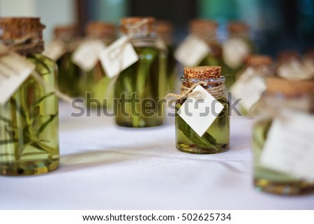 Miniature glass bottles of herb infused olive oil with labels on the table