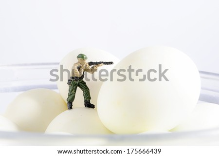 Miniature gunman on eggs - stock photo