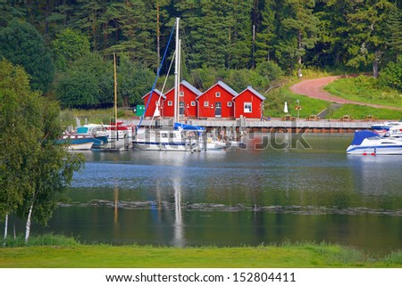 Miniature harbor in Kastelholm (Aland Islands) with nice red cabins. - stock photo