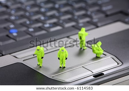 Miniature HAZMAt (hazardous materials) team inspects a laptop computer for viruses, spyware, and trojans. Computer security concept. - stock photo