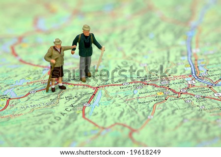 Miniature hikers standing on a map. - stock photo