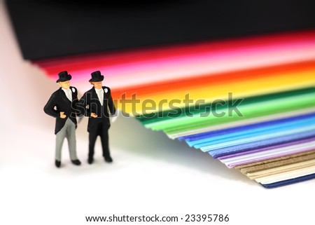 Miniature homosexual couple in tuxedos standing next to rainbow colored paper. Gay/same sex marriage concept. - stock photo