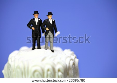 Miniature homosexual couple standing on top of a wedding cake. Gay/same sex marriage concept. - stock photo
