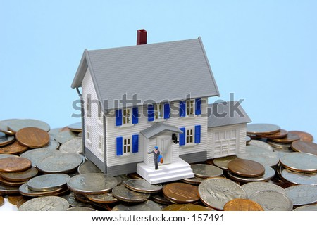 Miniature House and Change.  Home Savings / Mortgage Concept.  See Portfolio For Similar Concepts