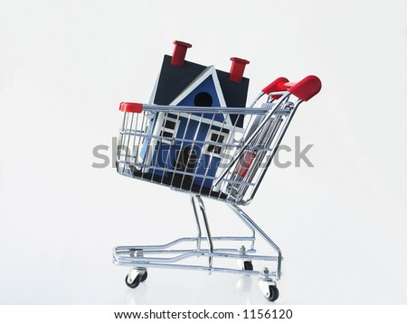 Miniature house in a shopping cart isolated on white illustrating shopping for a home. - stock photo