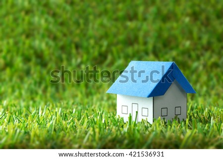 Miniature house model on green field for real estate industry