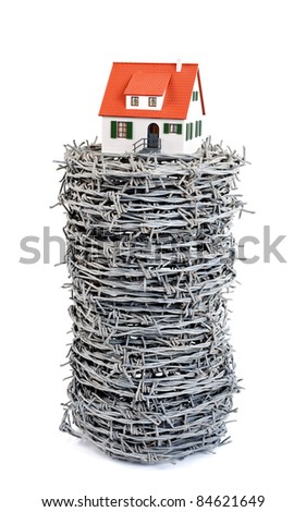 Miniature house with barbed wire, concept - stock photo