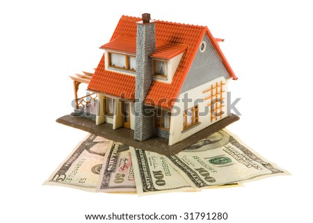 Miniature house with dollars isolated on white background