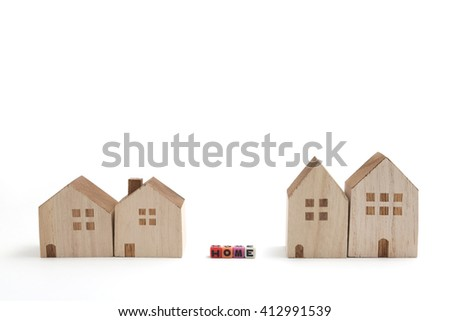 Miniature houses with alphabet blocks that spell home on white background.