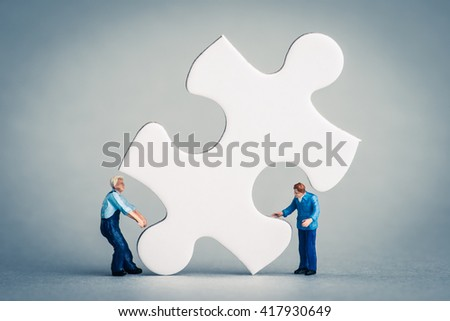 Miniature human carry a piece of the jigsaw puzzle