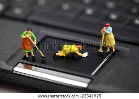 Miniature maids or cleaning women on a laptop computer. They are cleaning viruses, spyware and trojans. Computer anti-virus and security concept. - stock photo