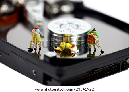 Miniature maids or cleaning women on an open computer hard drive. They are cleaning viruses, spyware and trojans. Computer anti-virus and security concept. - stock photo