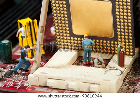 Miniature Maintenance Team. A team of miniature toy figurines busy with repair and maintenance. - stock photo