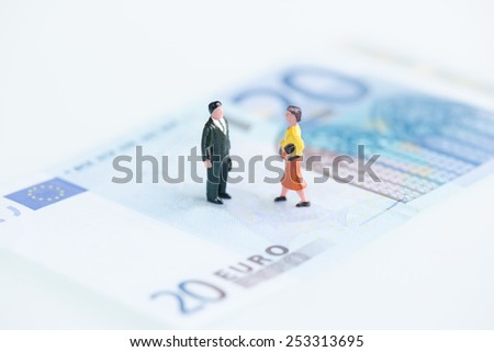Miniature man and woman on Euro banknote  - stock photo