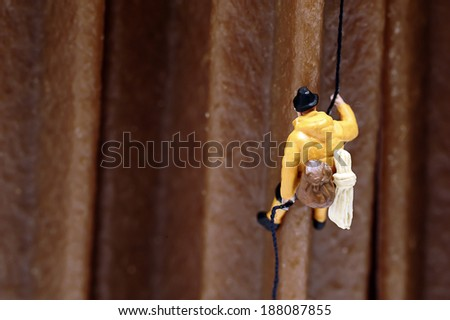 Miniature man climbing - stock photo