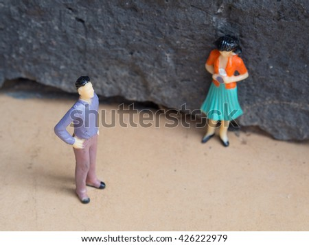 Miniature man is turned away from a miniature woman. They have a conflict in their relationship.