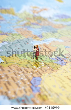 miniature man on map - stock photo