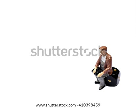 Miniature man sitting on dice isolated on white with room for copy space, gambling concept - stock photo