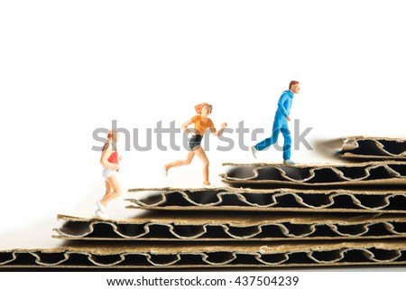 Miniature man who is running the stairs of cardboard - stock photo