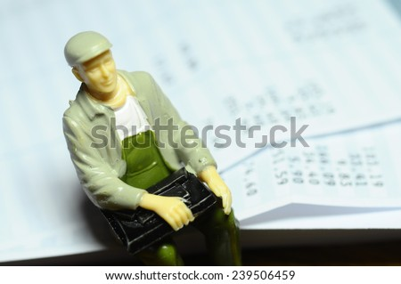 Miniature man with a cap sitting on payroll - stock photo