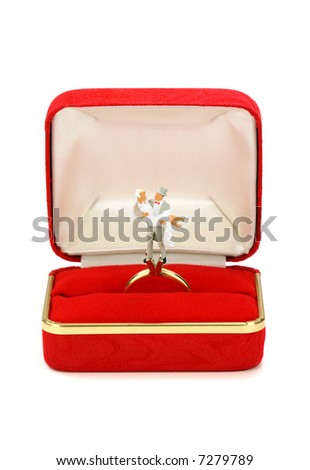 Miniature married couple stand on a wedding ring where a diamond would normally be. The ring box is red and against a white background. - stock photo