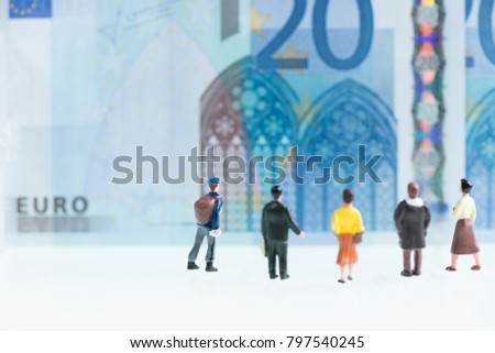 Miniature men and women looking at Euro banknote