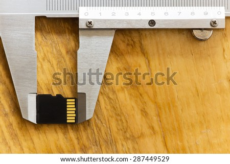 miniature micro sd card is measured with a caliper - stock photo