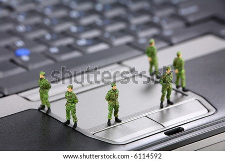 Miniature military soldiers are guarding a laptop from viruses, spyware and identity thieves. Computer security concept.
