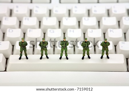 Miniature military soldiers are standing on a computer keyboard guarding it from viruses, spyware and identity thieves. Computer security concept. - stock photo