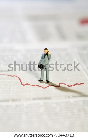 Miniature Model Businessman And Graph on the telephone discussing the statistics. - stock photo