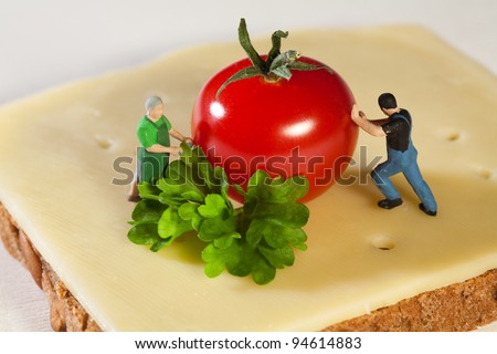 Miniature model figurines preparing a fresh cheese sandwich with herbs and tomato. - stock photo