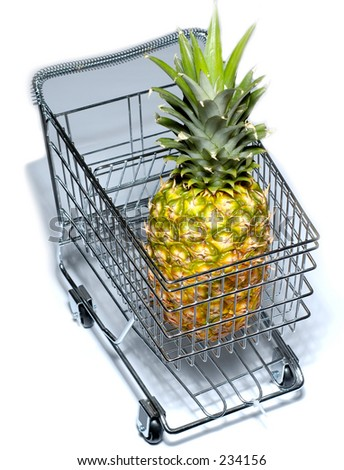 Miniature model of a shopping cart with pineapple inside. - stock photo