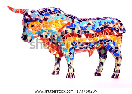 Miniature multicolored statue of bull in Gaudi style - traditional souvenir from Barcelona(Spain) . This is not art object, only inexpensive spanish gift.  - stock photo